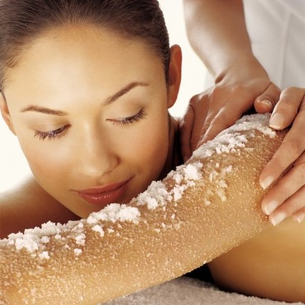 Woman having salt scrub spa treatment on her arm