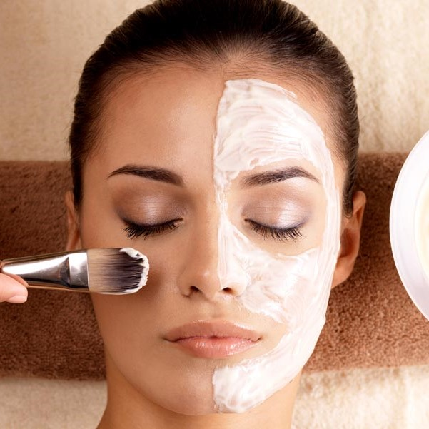 Photo of woman having facial with white masque on half of her face