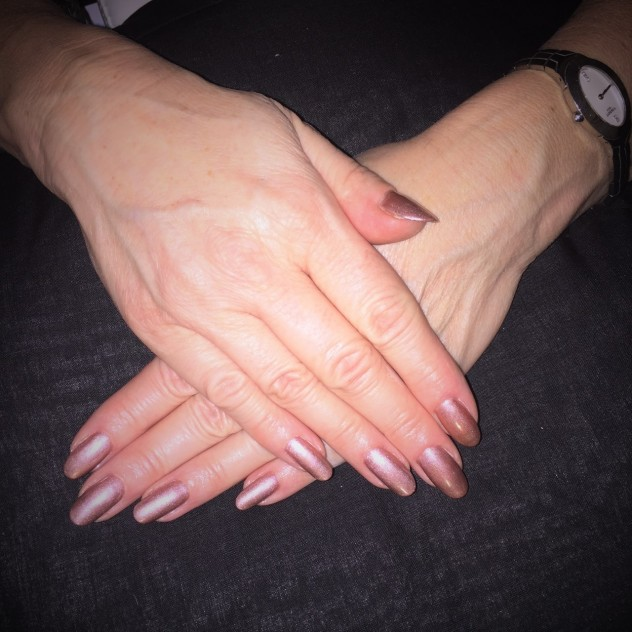 Shiny dusky/pale pink, long Gelish gel nails on a dark background