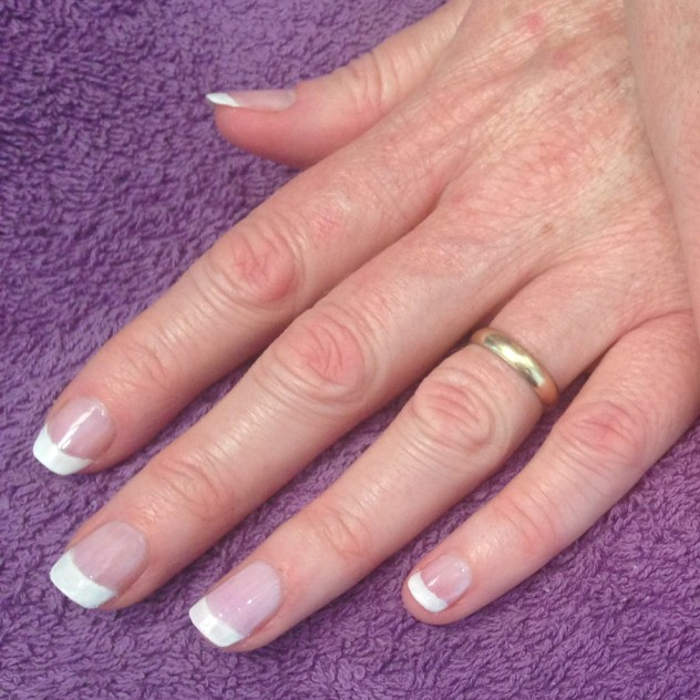 Woman's hand with ring and french polish on purple background