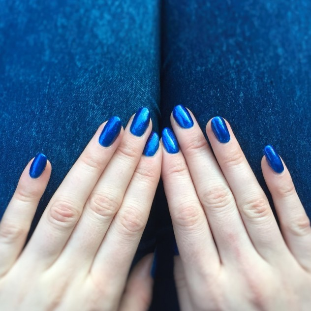 Blue Gelish gel polish on woman's nails, pale hands against a denim jeans background