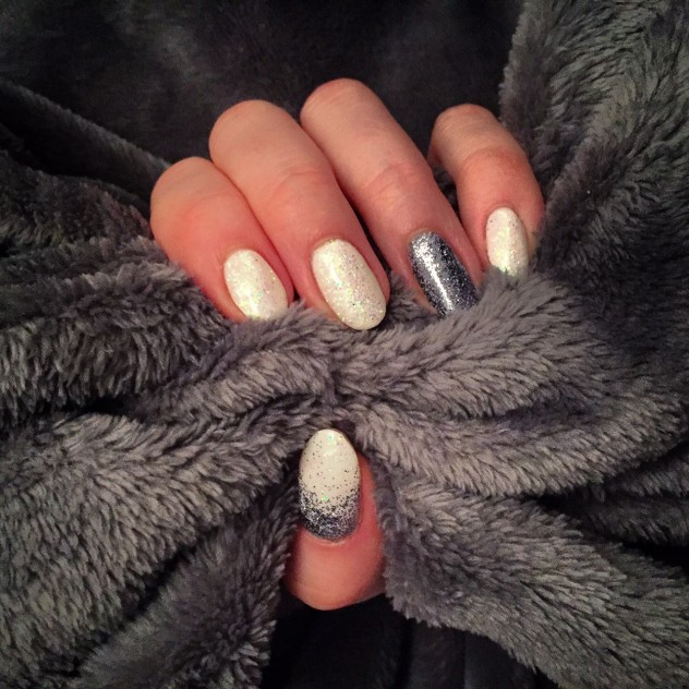 White and silver glittery gel nails on a grey background