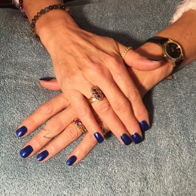 Dark blue Gelish gel nails on a grey background