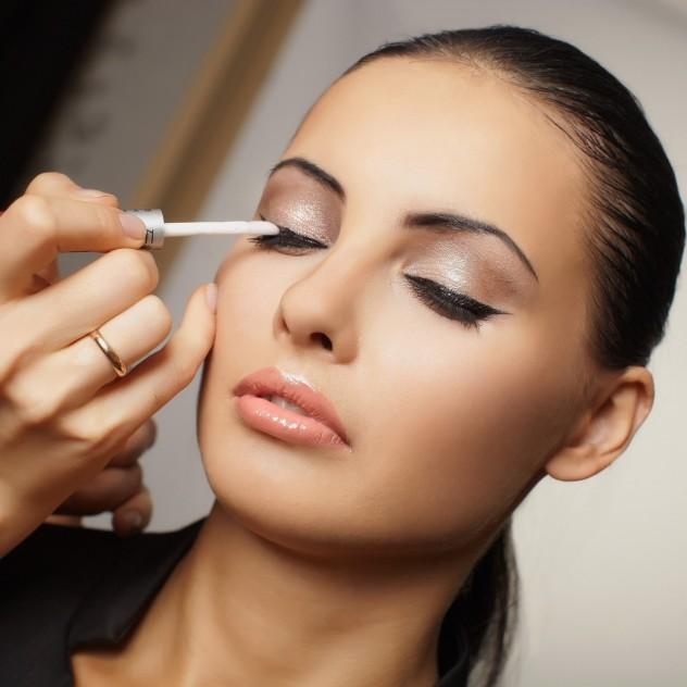 Pretty woman having eye make up put on