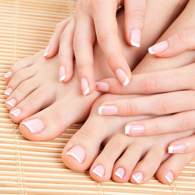 Woman's hands holding her feet, both with french manicure and french pedicure