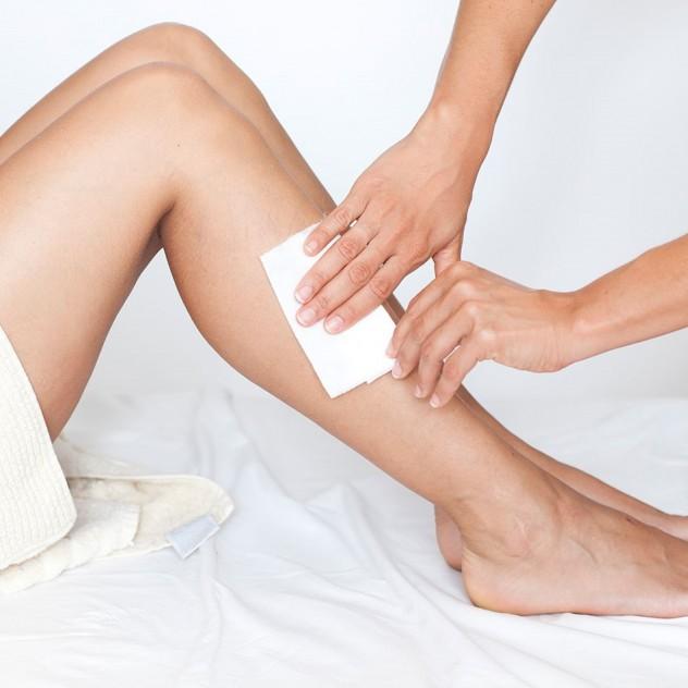 Woman having her legs waxed
