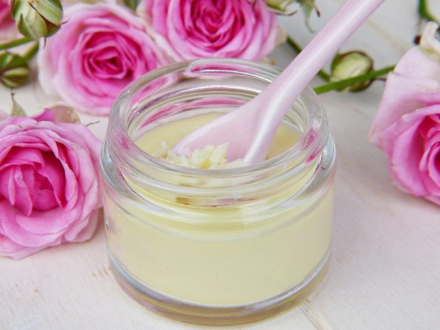 Moisturiser in a glass tub surrounded by flowers