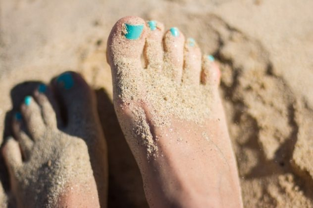 Womans feet in the sand with bright blue nail varnish on her toes