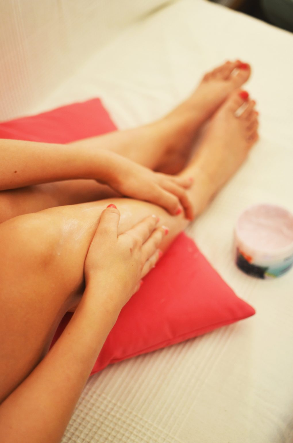 woman holding her bare leg after waxing or moisturising